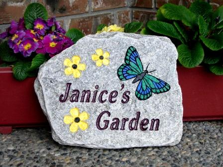 Yellow flowers in the green butterfly engraved on Genesis garden stone