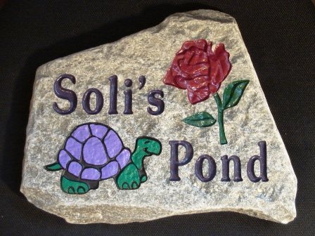 Garden stone engraved with a rose and a turtle