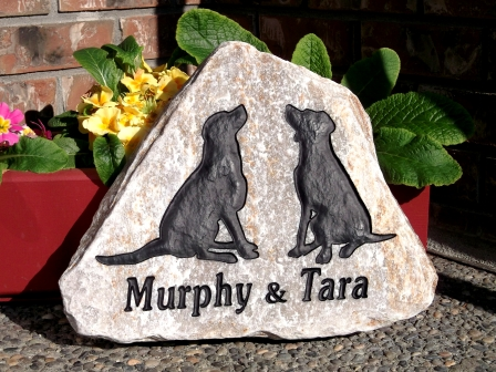 2 dogs remembered on a garden stone